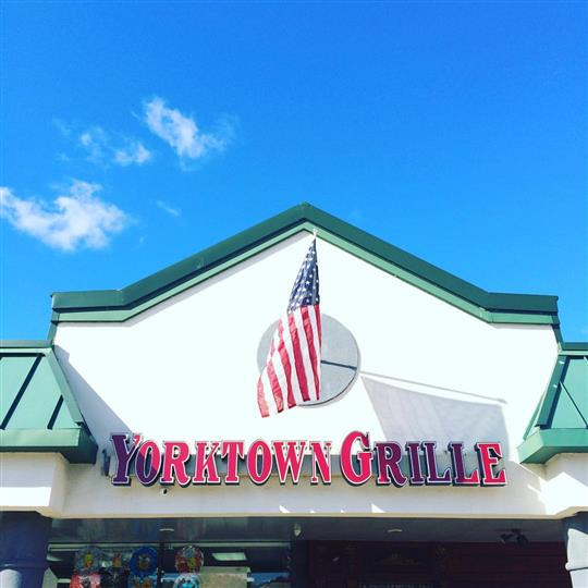 Yorktown grille sign and american flag over front entrance