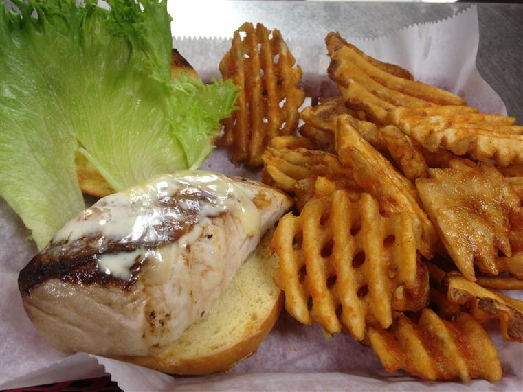 Grilled chicken sandwich with cheese and lettuce and waffle fries