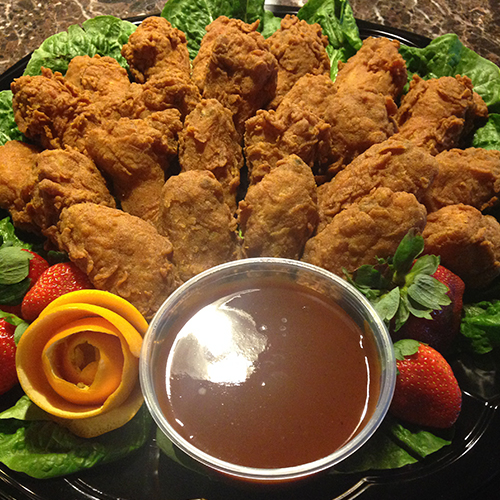 Chicken wings served on a bed of lettuce with a dipping sauce in the middle