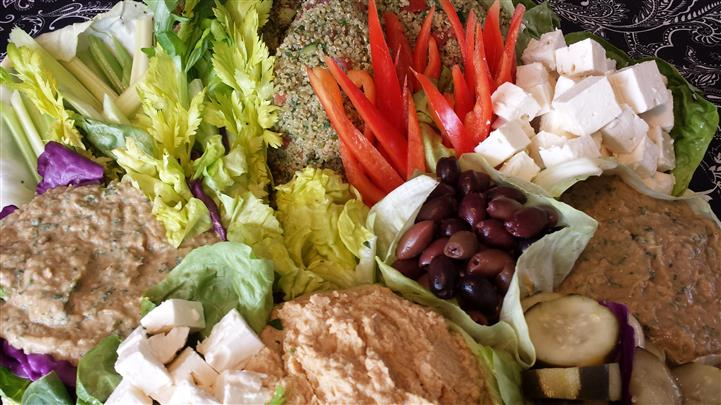 Salad tray filled with a mix of sauces, cheese bites, olives and begetables
