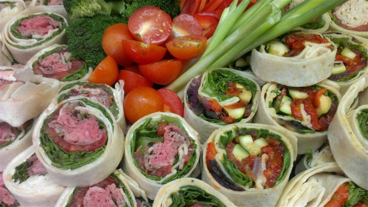 Tray full of bite-sized wrap rolls served with vegetables