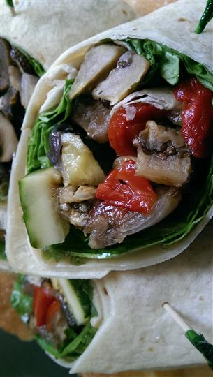 Halved wrap with grilled vegetables and lettuce