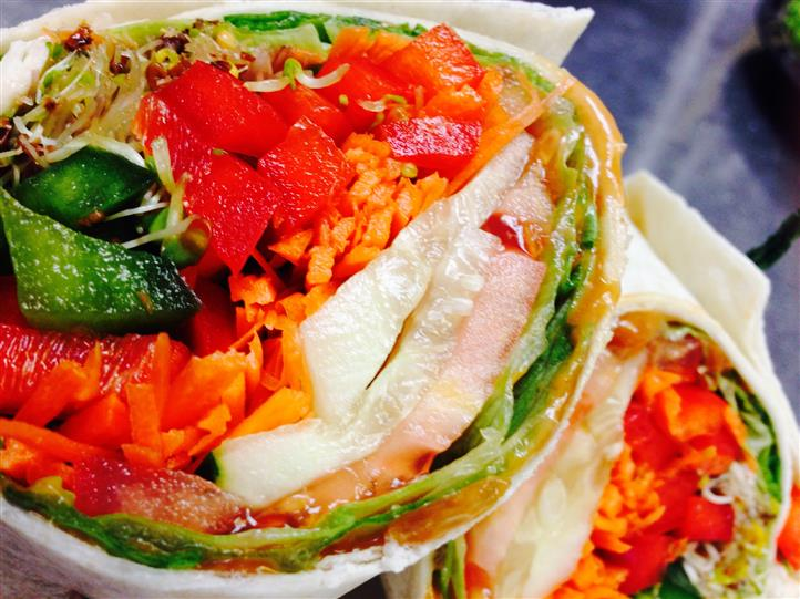 Halved veggie wrap with tomato, zucchini, carrots, peppers and lettuce