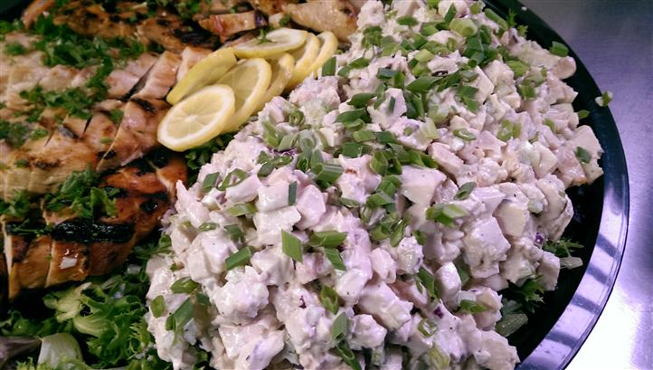 Tray with variety of cooked meats sprinkled with coriander and served with lemon slices