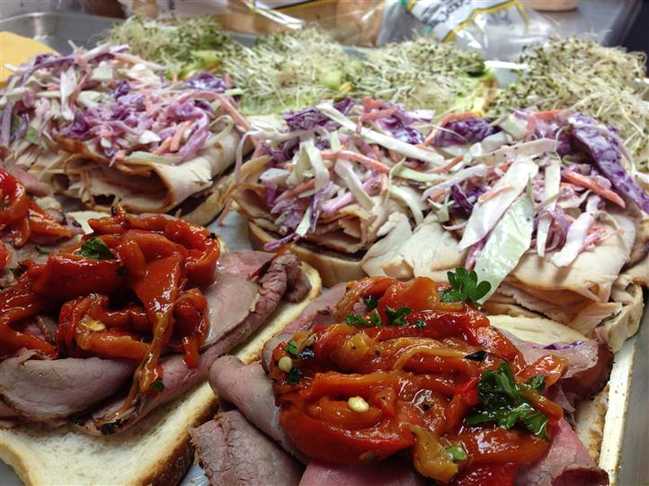 Variety of open faced cold cut sandwiches laid out in a tray