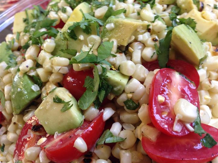 Corn salad with avocado bits and cherry tomatoes sprinkled with coriander