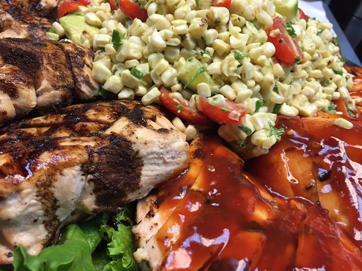 Grilled meat covered in red sauce served with corn salad