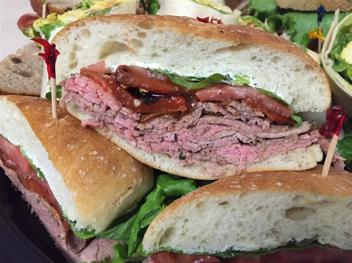 Cold cut meats sandwiches piled in a tray