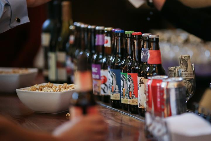 An array of beer bottles laid out in line over the bar counter with snacks in the background