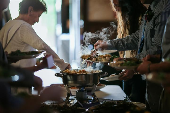 People reaching for food around a buffet tables
