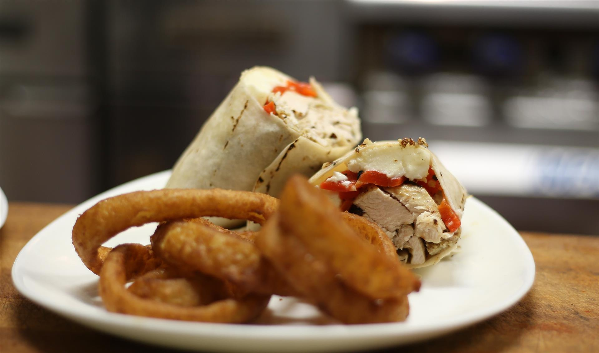Grilled Chicken, Red peppers, Fresh Mozzarella in a Wrap, with onion rings.