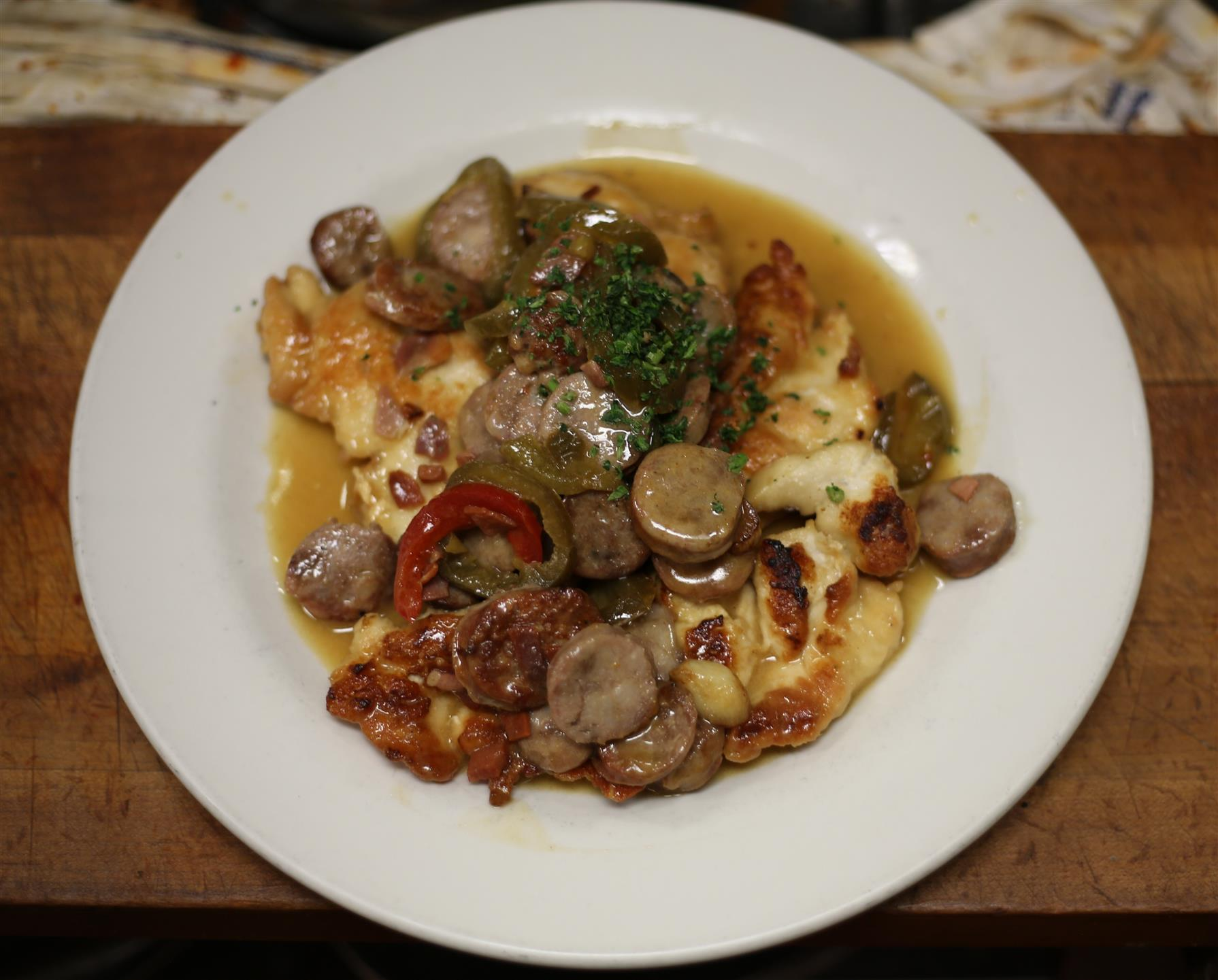 Chicken Scarpariello. Boneless chicken sauteed with sausage, prosciutto and garlic in lemon, butter and white wine.