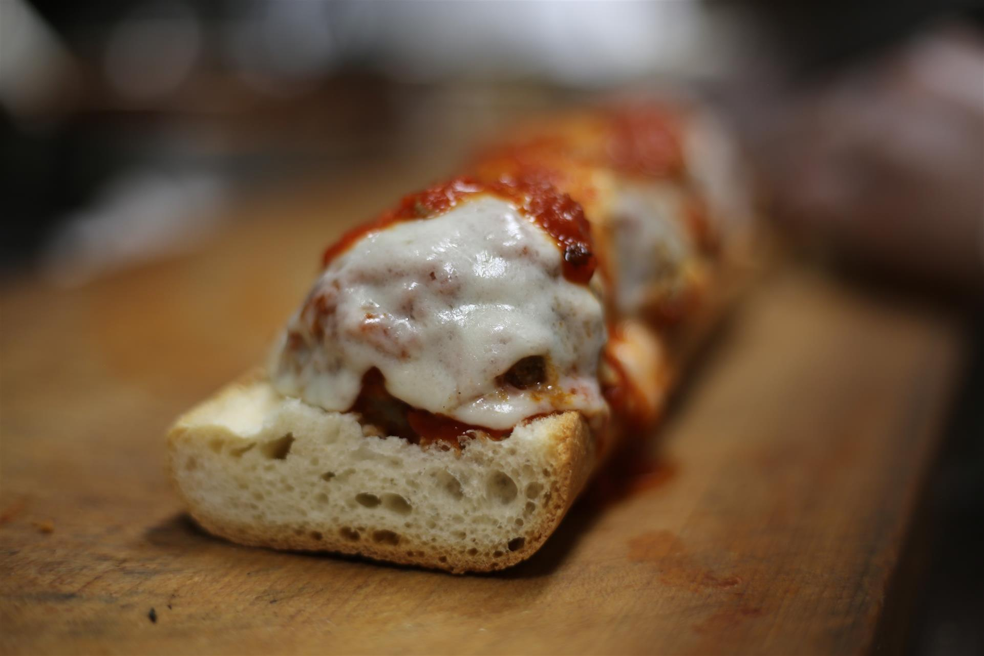 Open meatball parmigiana hero.