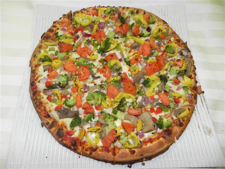 Personal vegetable pizza topped with broccoli, tomatoes, and peppers