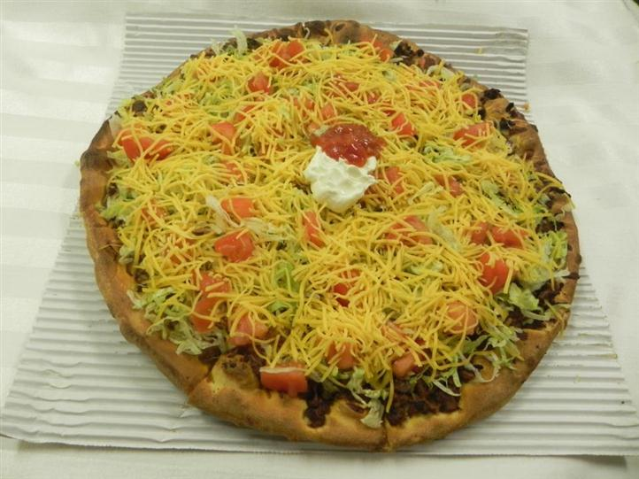 Taco Pizza topped with ground beef, lettuce, tomatoes, shredded cheese, and sour cream