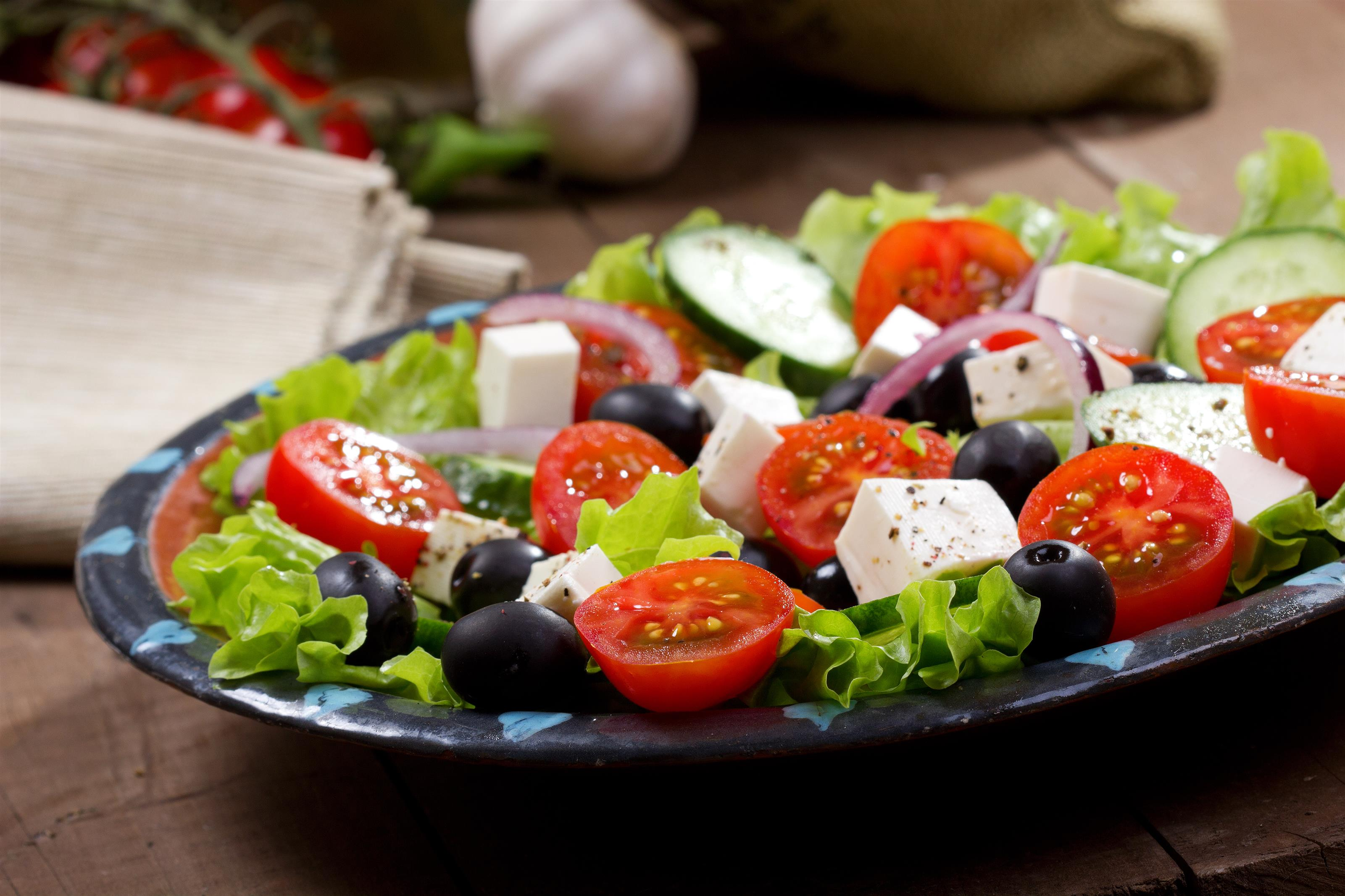 garden salad with lettuce, tomatoes, olives and cheese