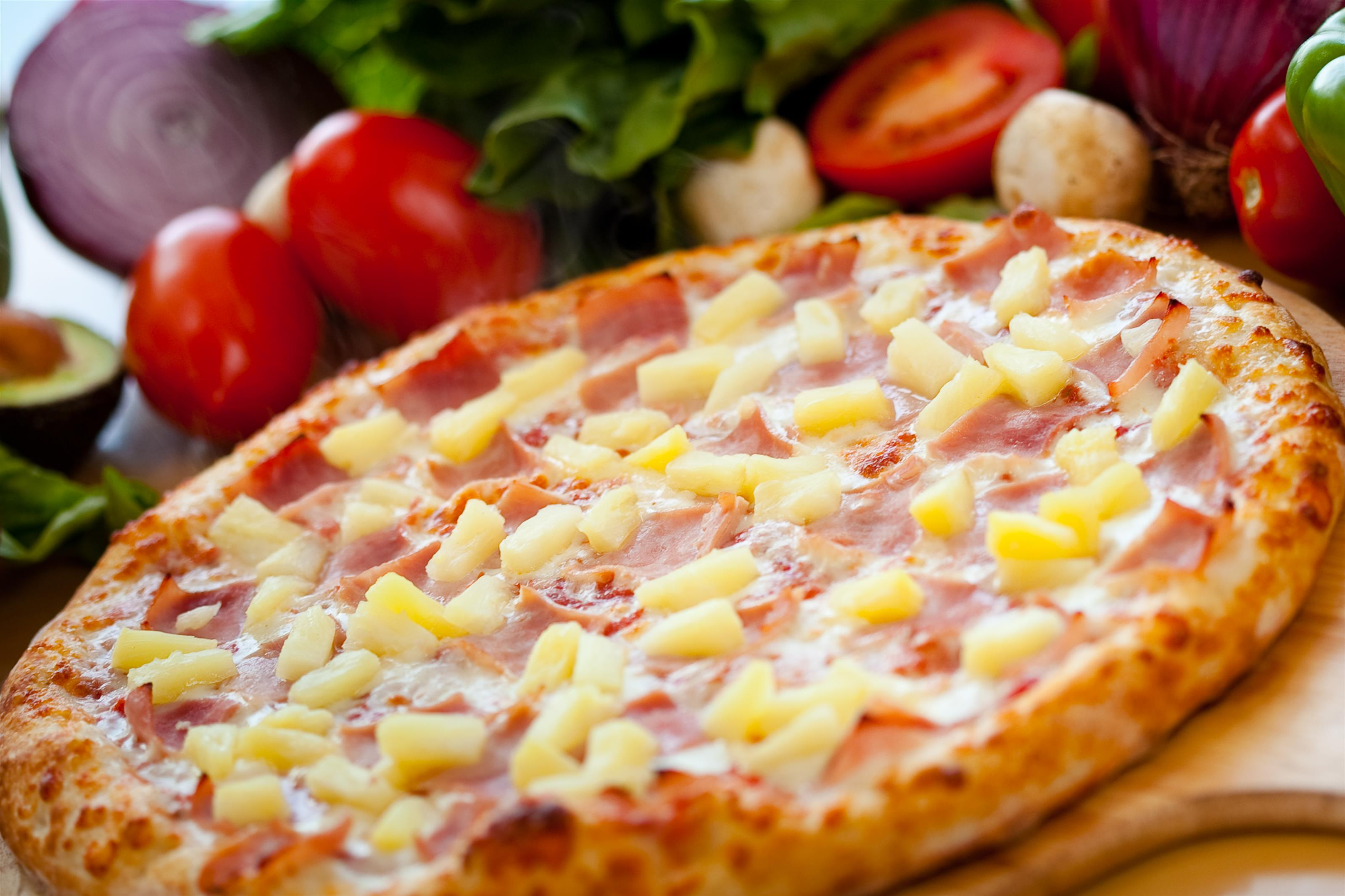 large cheese pizza topped with pineapple and ham