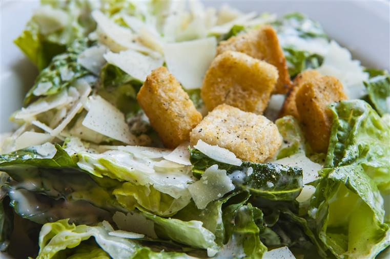 caesar salad with croutons and topped with shaved parmesan cheese