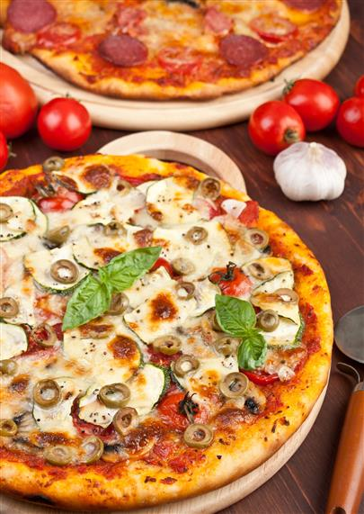 two pizzas on a table with tomatoes and garlic