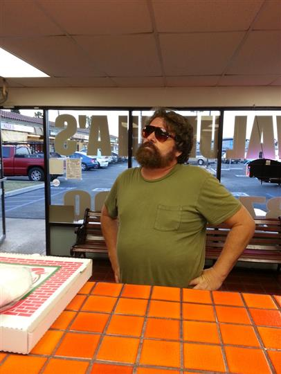 actor zach galifianakis standing in front of the store counter looking at the menu