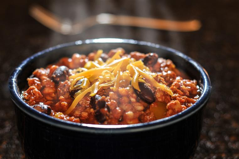 bowl of chili with melting cheese on top
