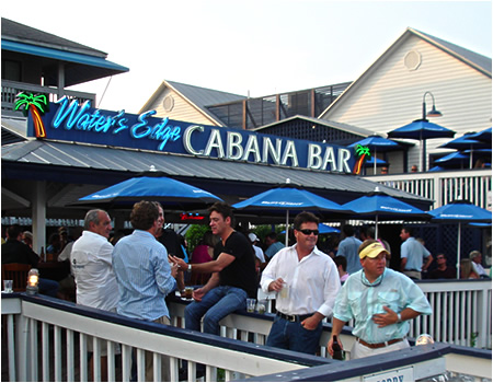 Water's Edge cabana bar outdoors with patrons talking and holding drinks