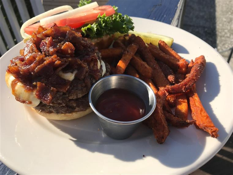 Hamburger with cheese, bacon, lettuce, onions, tomatoes, pickle and side of sweet potato fries