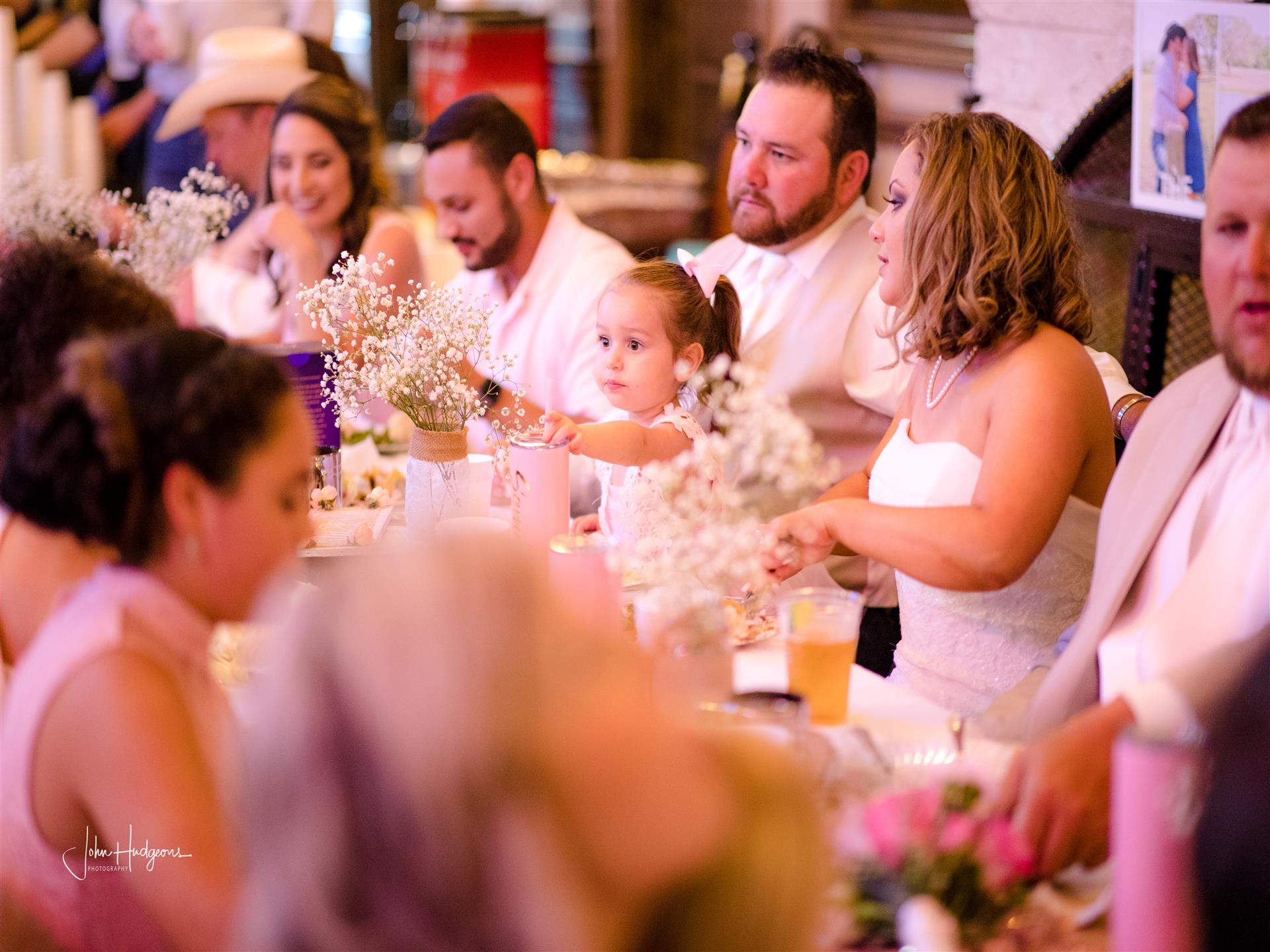 Guests sitting at long table at wedding event