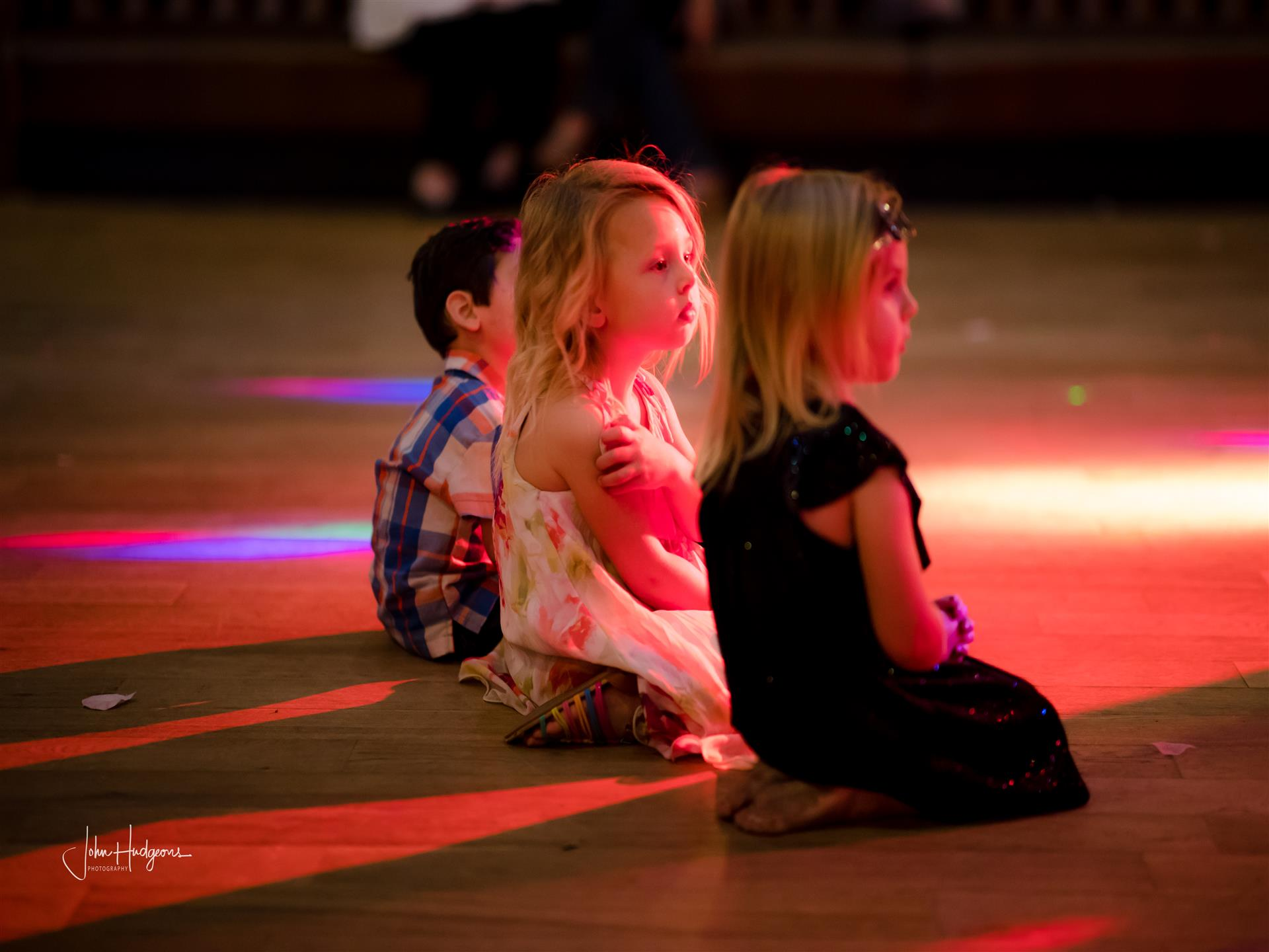 Three children sitting on dance floor