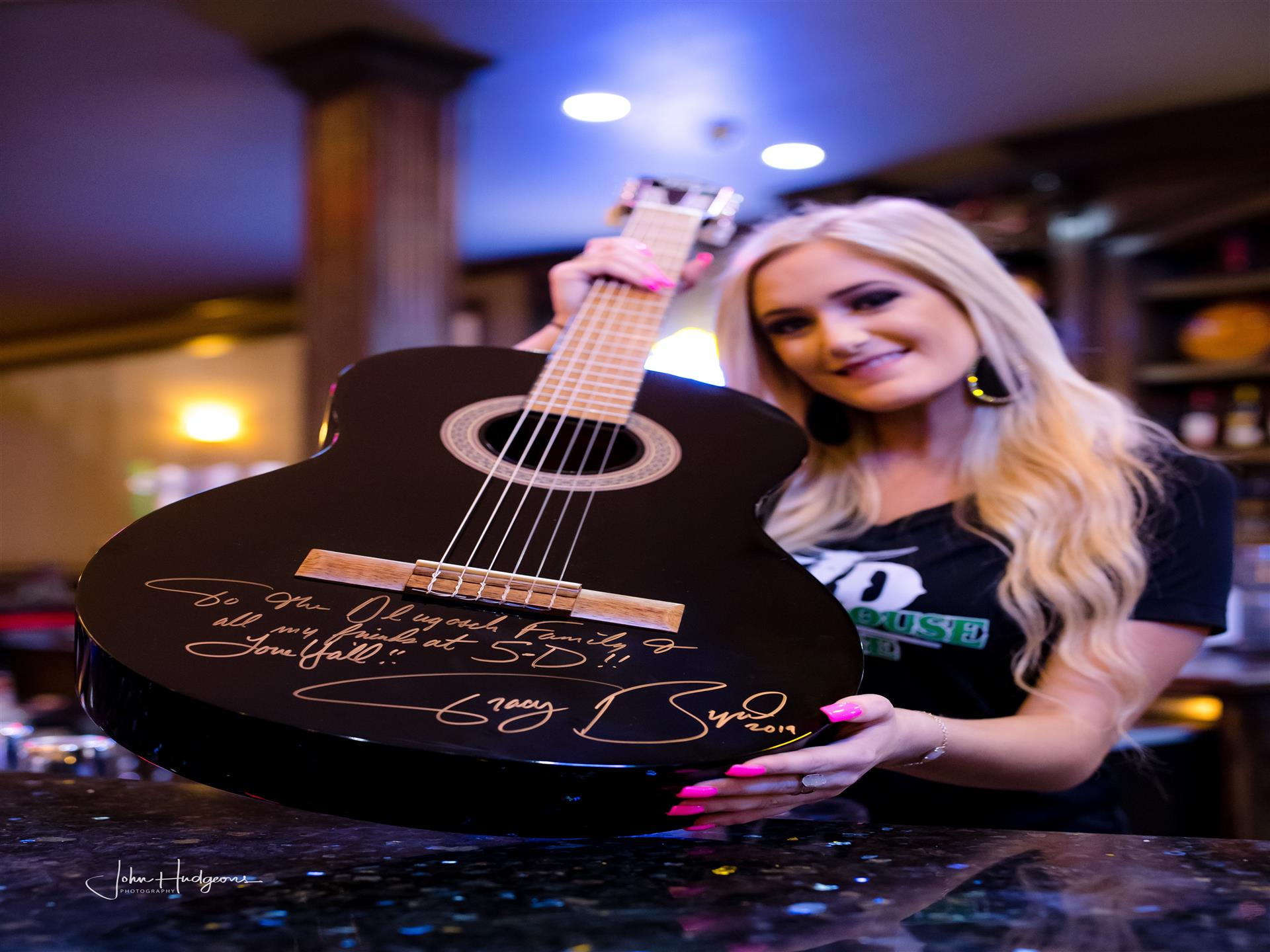 Staff holding guitar with multiple signatures on it