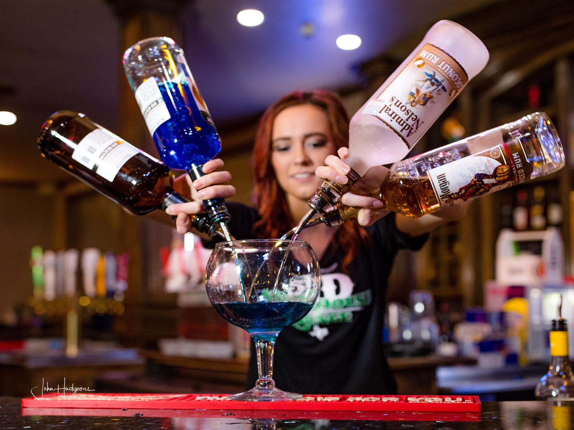 Bartender with four alcohol bottles pouring into large bowl glass
