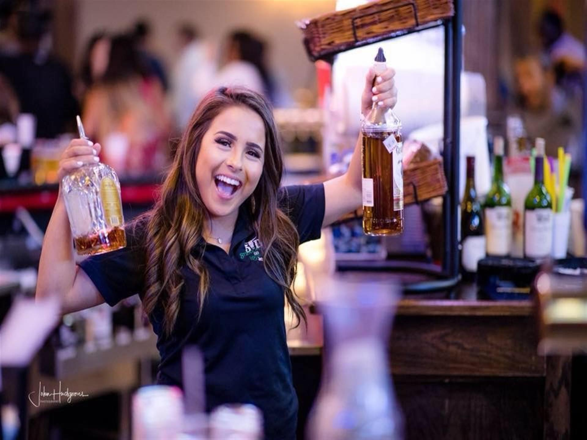 Bartender smiling and holding up a bottle of alcohol in each hand