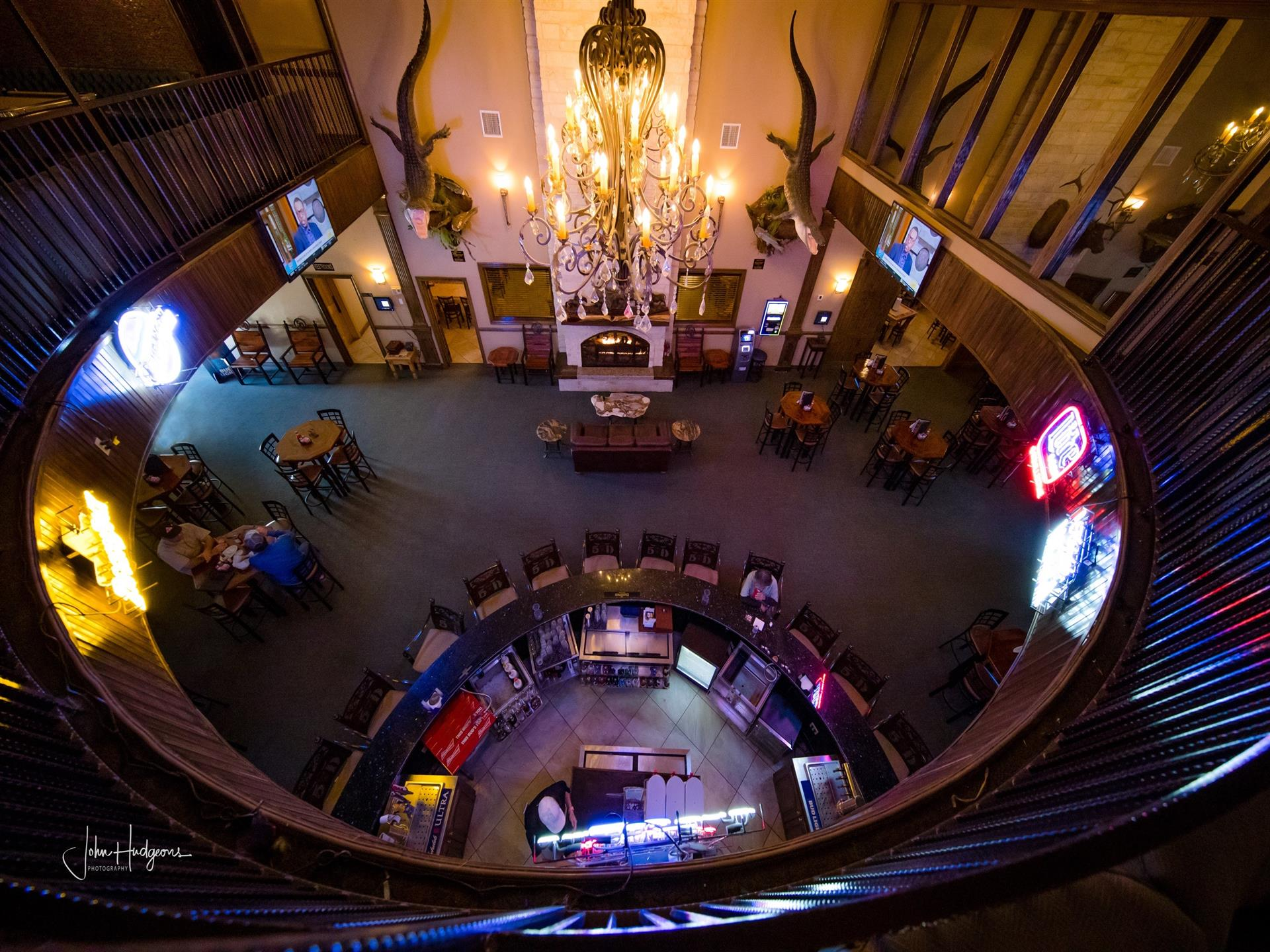 Panoramic photo from second floor balcony inside restaurant looking down on bar