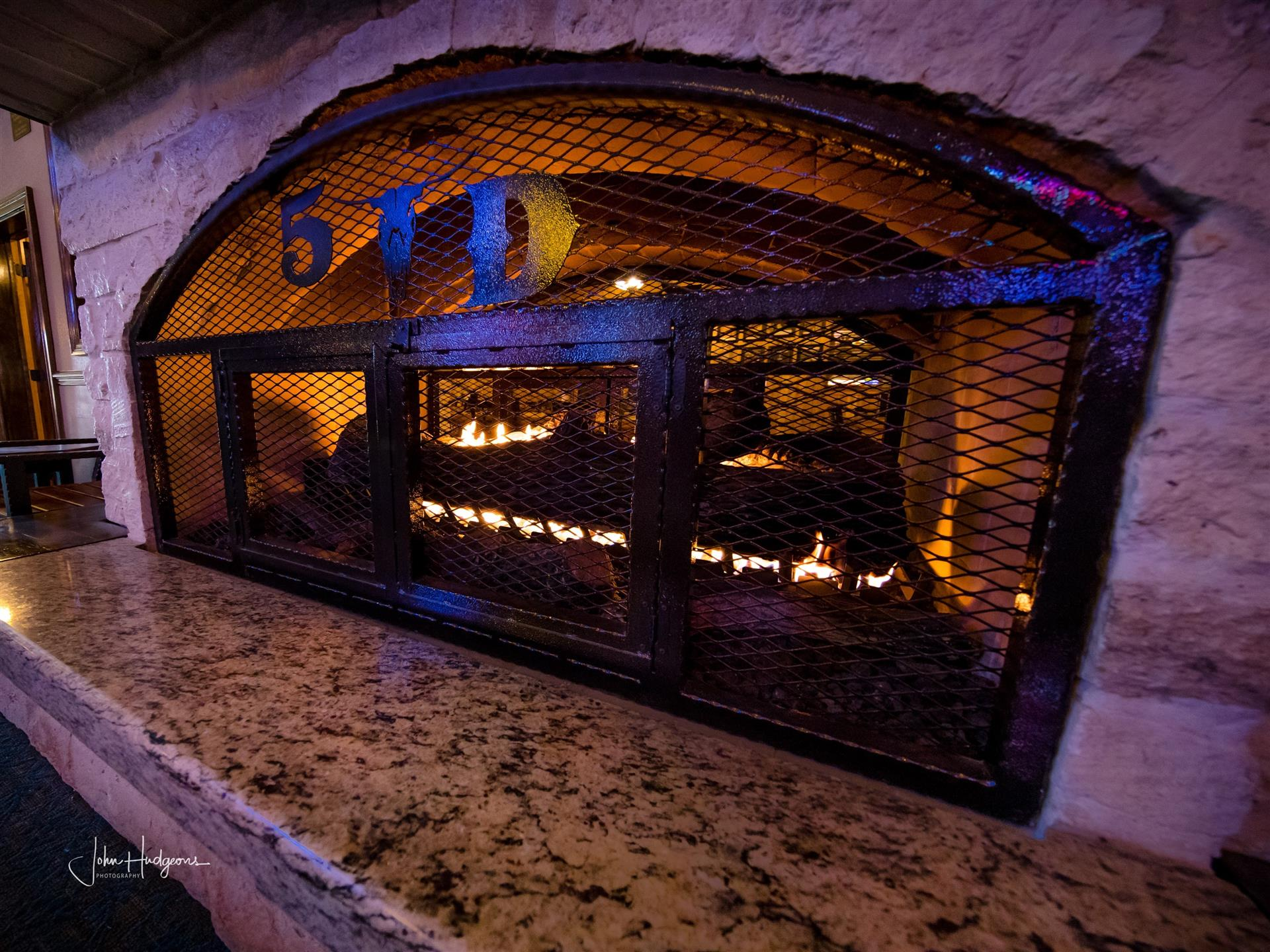 Fireplace inside restaurant with 5D logo on it