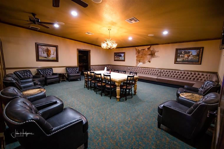 Inside of the longhorn suite that shows multiple couches and chairs and a dining table in the middle surrounded by 10 chairs