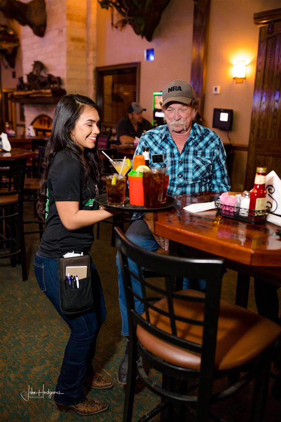 Waitress bringing a tray of drinks to a customer sitting at a table