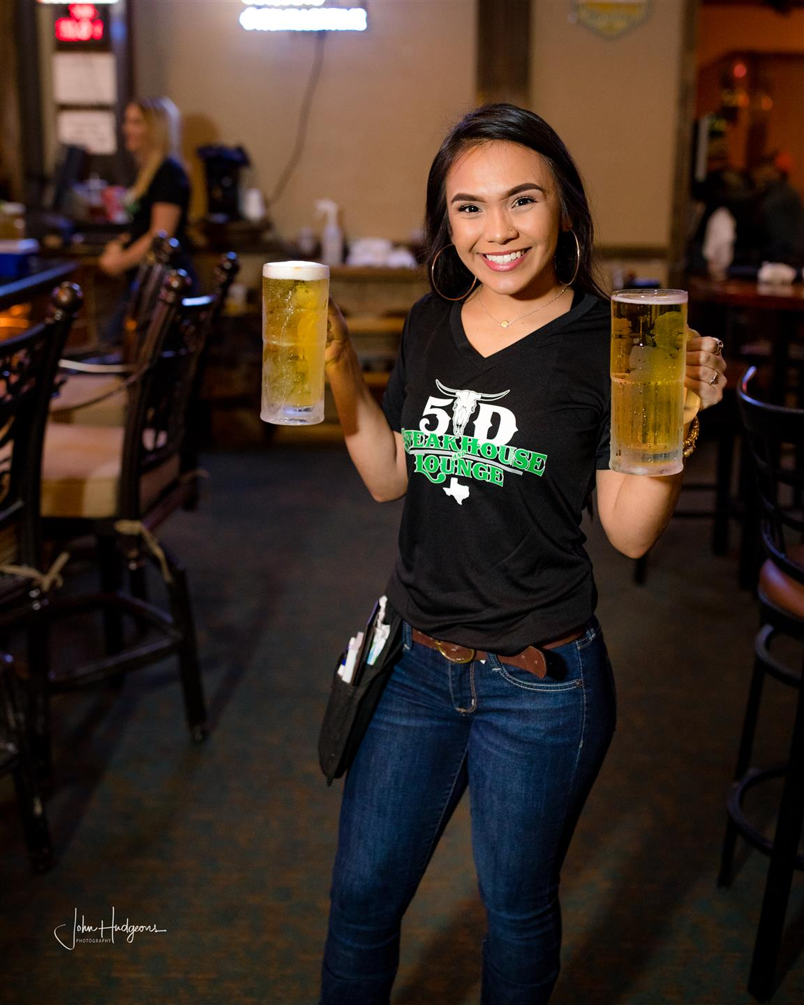 Waitress posing with a beer in each hand