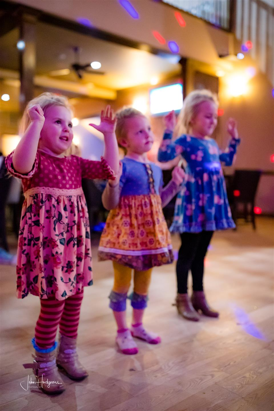 Three children dancing on dancefloor