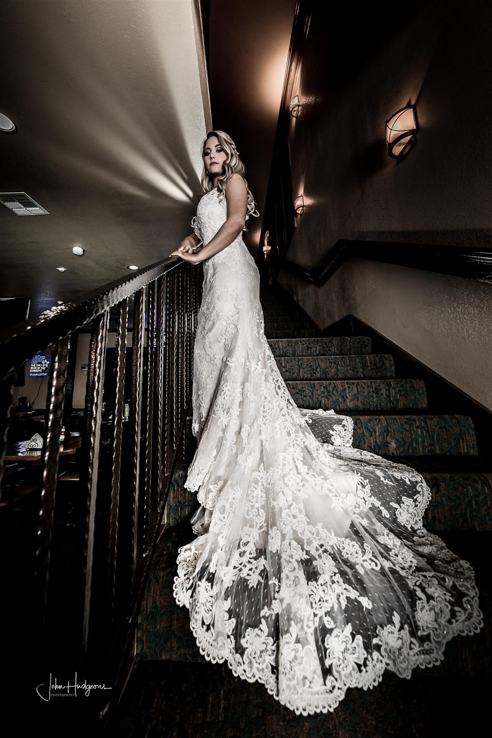 Bride on staircase with wedding gown