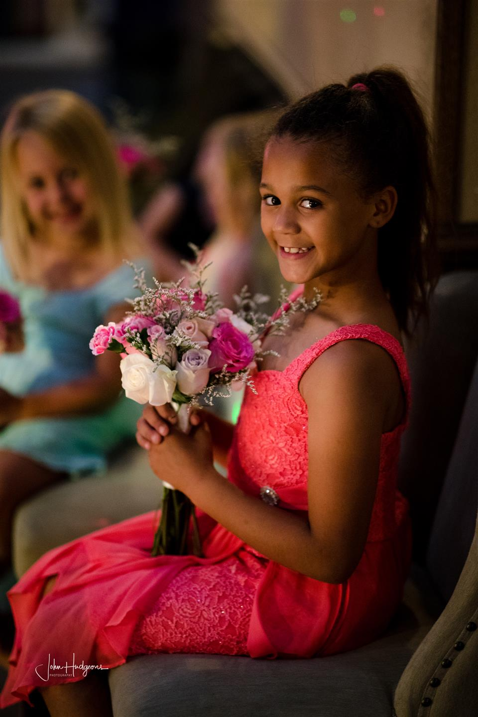 Young girl sitting in chair holding wedding flowers