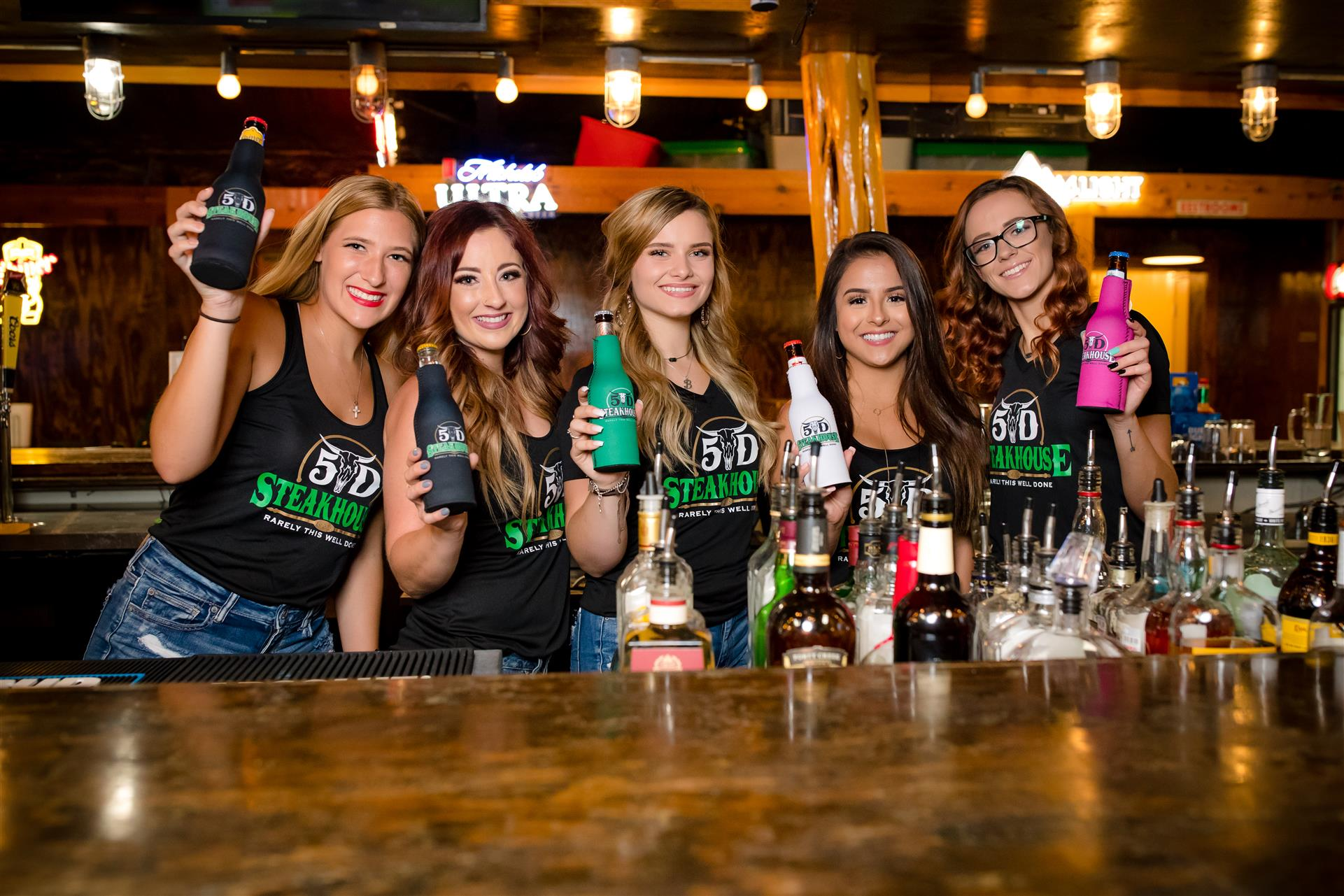 5 female bartenders each holding a beer