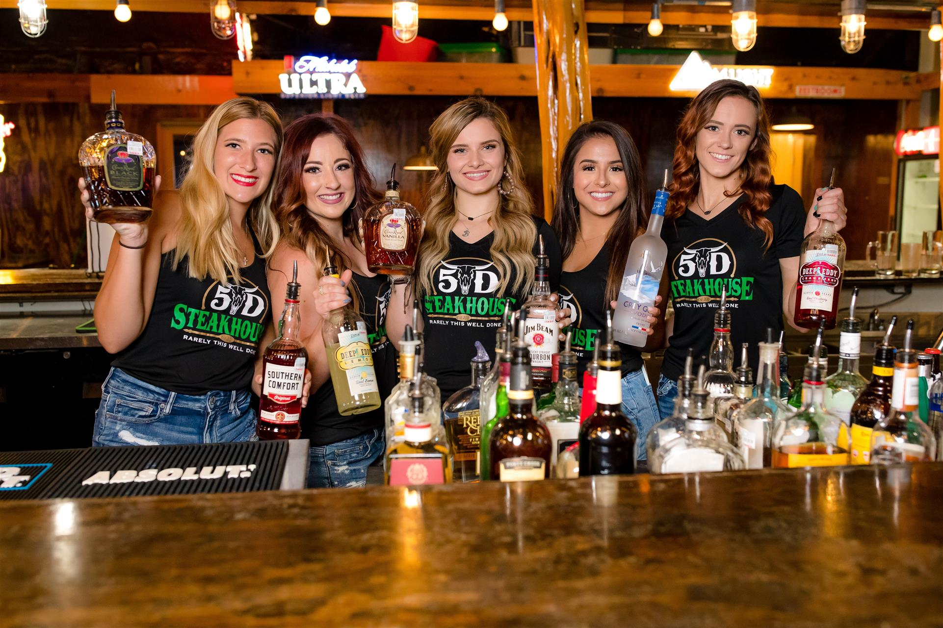 5 female bartenders each holding a bottle of liquor