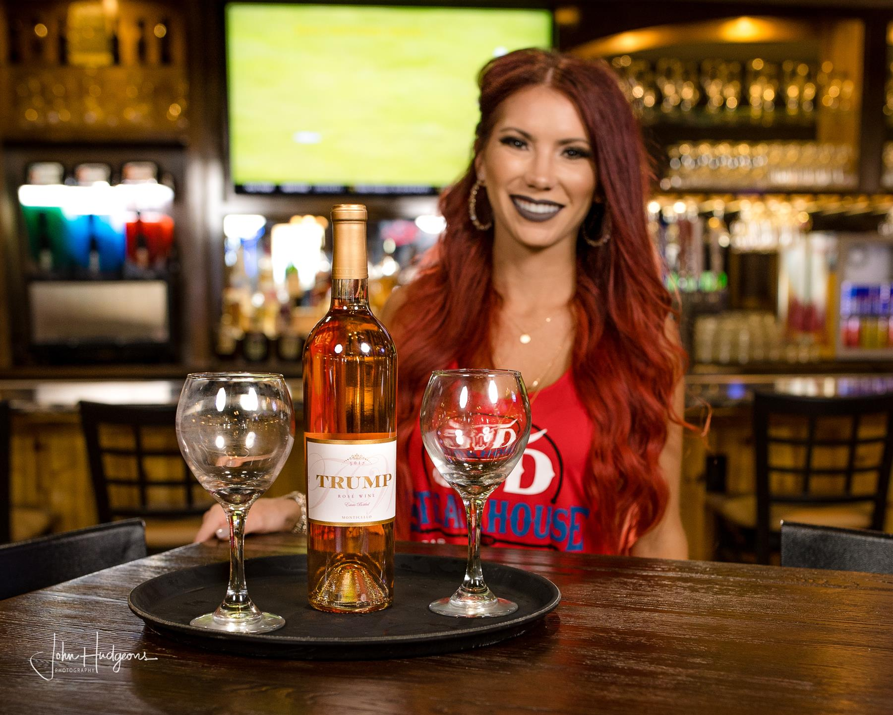 Cocktail waitress posing in front of bar table with serving tray and bottle of wine