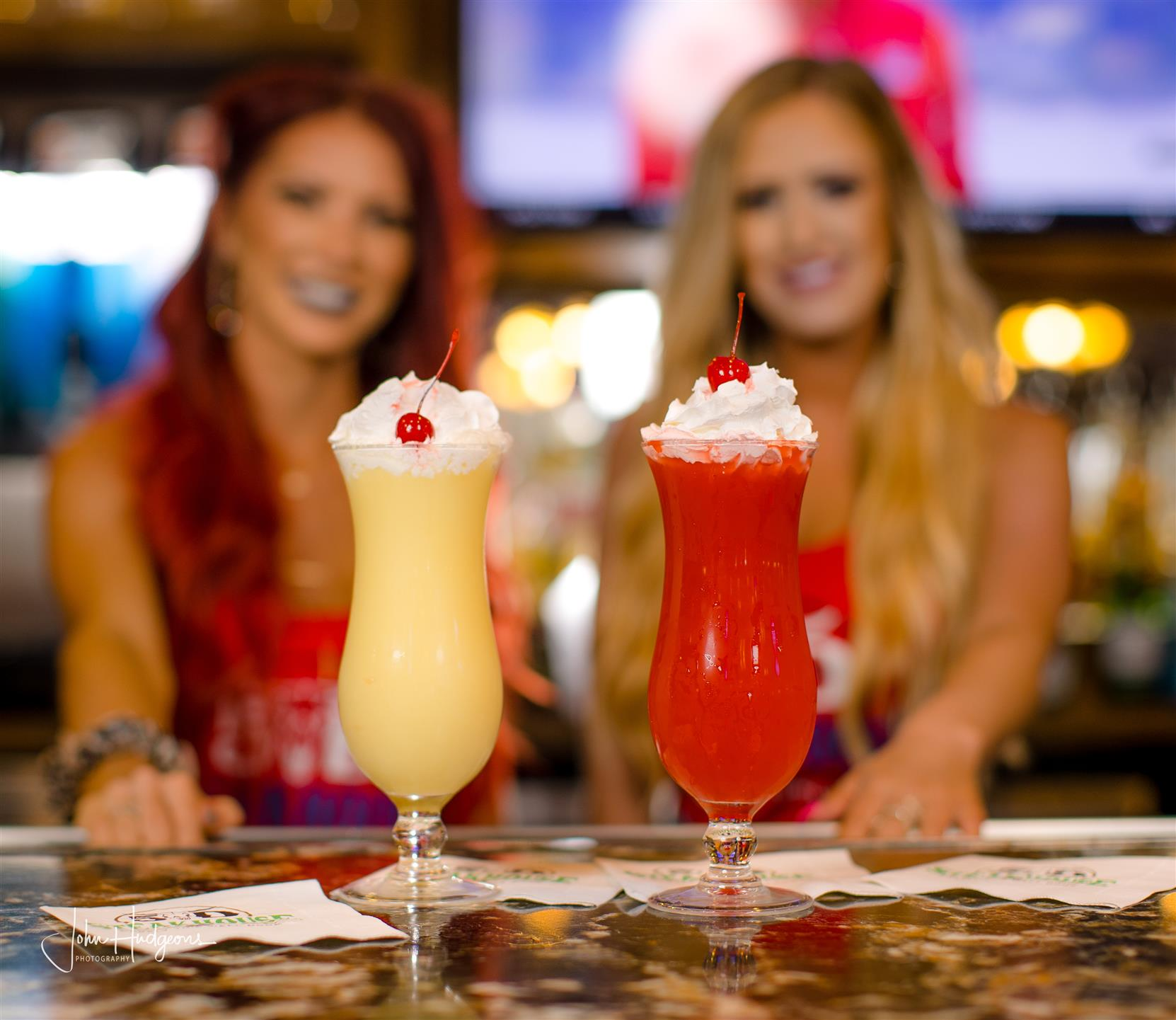 Two young waitresses standing behind bar top with 2 frozen drinks on top.