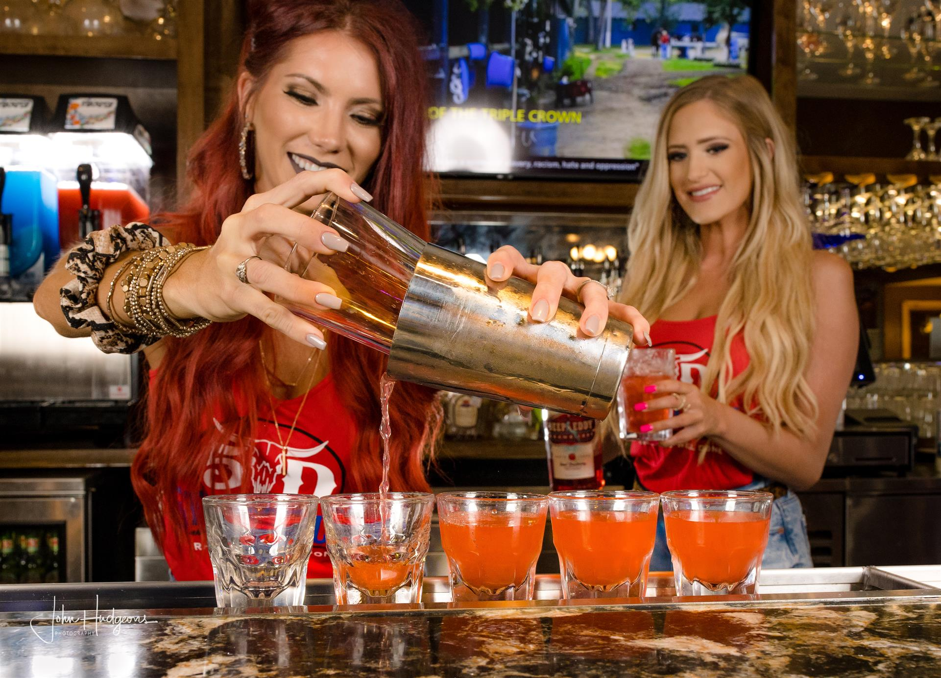 Two bartenders pouring shots