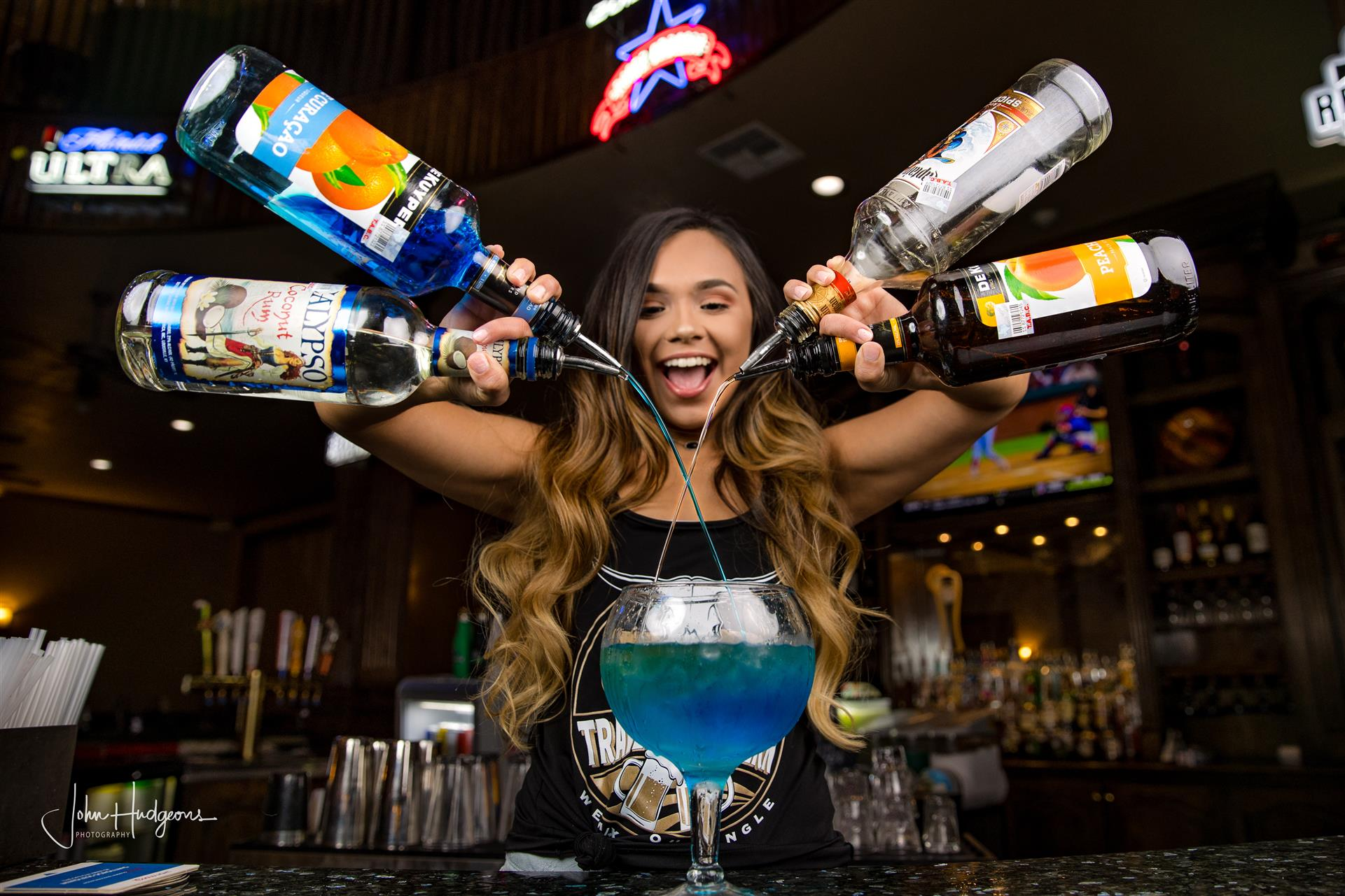 girl with 4 bottles in her hands pouring drinks