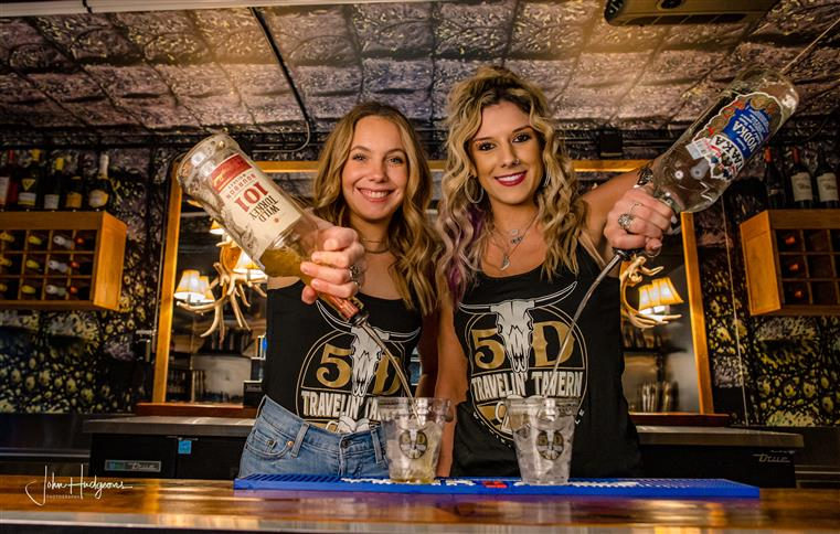 2 female bartenders pouring alcohol into cups behind the bar