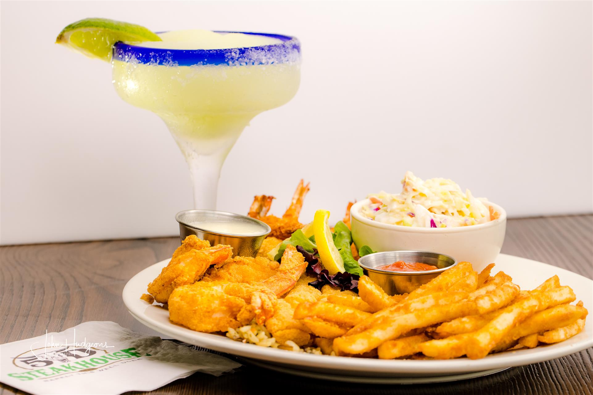 french fries with fried shrimp and coleslaw next to a margarita