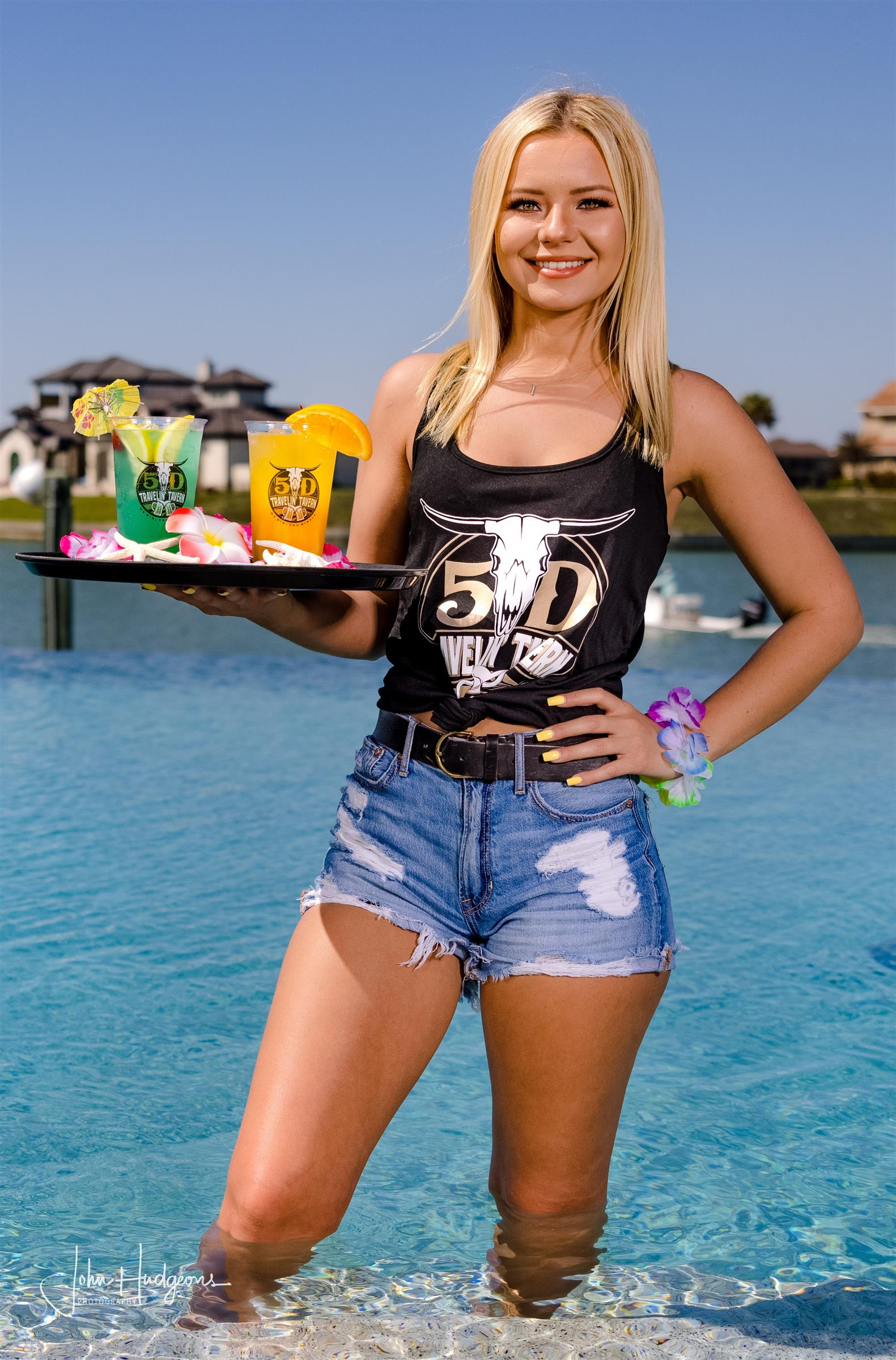 Girl wearing 5D Steakhouse shirt, holding two cocktails standing in a pool