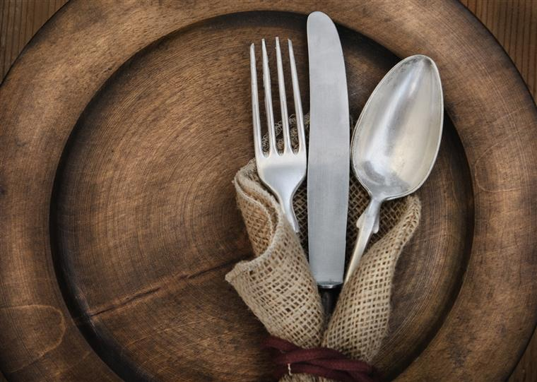 Fork, knife, spoon on rustic wood plate